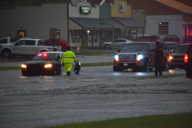Ardmore police wade through flood waters at the intersection of South Commerce Street and Stanley Avenue on Tuesday.