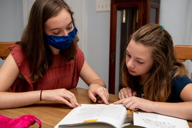 Alexa Scheetz, left, a Quakertown Community High School senior, listens as Evangeline Logan, 11, of Richalandtown, reads during an at-home tutoring session.