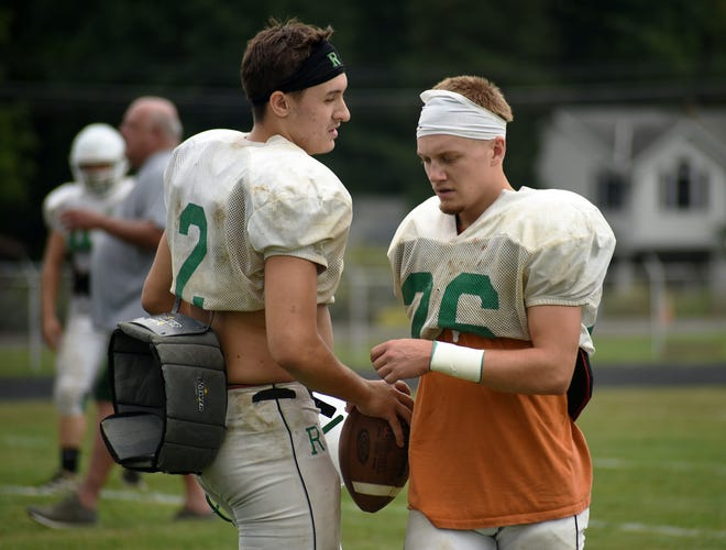 Riverside High School's Sam Hughes, left, talks with his cousin, Calvin Hughes, during practice on Aug. 31.