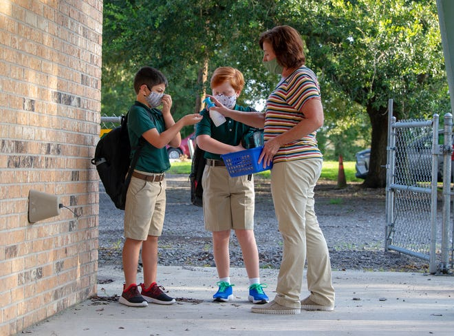 Karen Guillot gives hand sanitizer to second-grader Vince Naccio as second-grader Colt Daughtery waits for his turn on the first day of school at St. Charles Elementary in Thibodaux on Aug. 31.  Lafourche students will go back to attending school five days per week starting Monday.