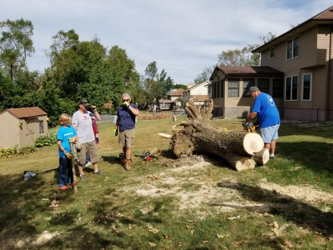 Volunteers with New Hope Church in Adel help clear a large tree from a home in Cedar Rapids.