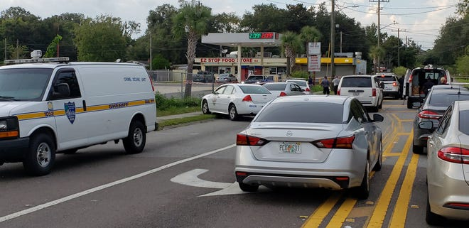Jacksonville police officers converge on the scene of a deadly double shooting Tuesday on Division Street.