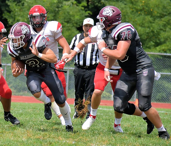 Woodride quarterback Ben Kiser (2)  looks for a block from lineman Allistair Larson (76) during the Bulldogs' 27-19 home loss to Field Aug. 29.