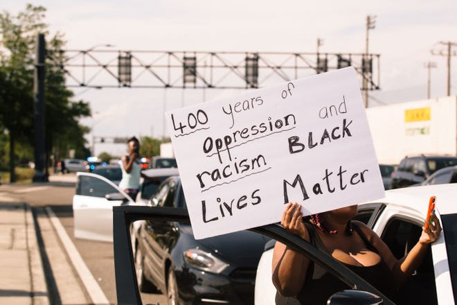 A protester holds a sign as cars sit backed up at the intersection of Memorial Boulevard and Florida Avenue in Lakeland on May 31. A day of peaceful protests in the city over the death of George Floyd turned into unrest as Lakeland police officers in riot gear and backed by armored vehicles deployed tear gas and pepper spray to end the hours-long demonstration.