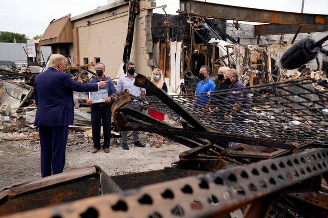 President Donald Trump talks to business owners Tuesday as he tours an area damaged during demonstrations after a police officer shot Jacob Blake in Kenosha, Wis.
