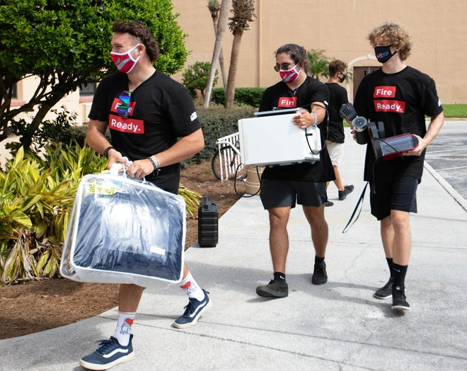 Southeastern University students Drew Bowker, from left, Mason Kump and Parker Drake carry their items as they move into a campus residence. The university opens the fall semester Wednesday with health measures in place.