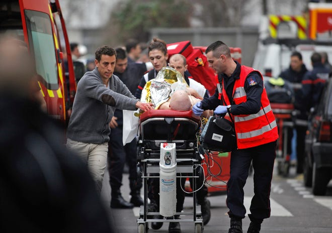 An injured person is transported to an ambulance in January 2015 after a shooting at the French satirical newspaper Charlie Hebdo's office in Paris. The January 2015 attacks against Charlie Hebdo and, two days later, a kosher supermarket, touched off a wave of killings claimed by the Islamic State group across Europe.