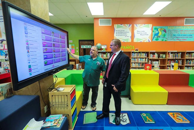 Deputy Superintendent Keith Oswald (right) checks out a Google panel at North Grade Elementary in Lake Worth in 2018. The panels come with cameras that can be used in remote learning. (Bruce R. Bennett / The Palm Beach Post)
