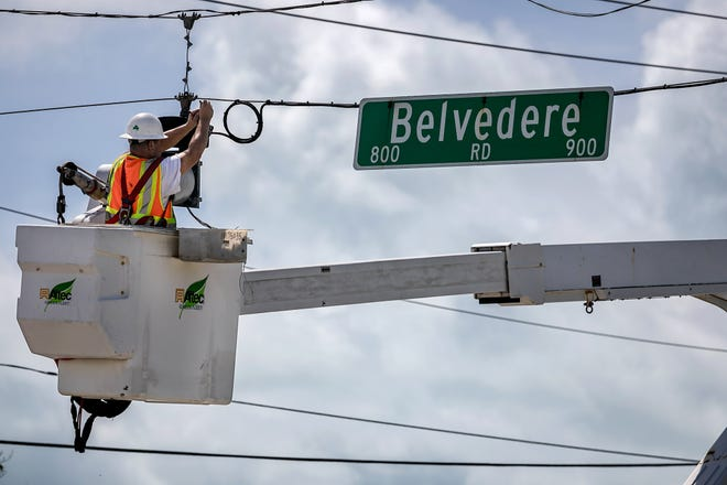 A worker repairs a stoplight along Belvedere Road at the intersection of Parker Avenue after Hurricane Irma in West Palm Beach photo from September 11, 2017. Greg Lovett / The Palm Beach Post