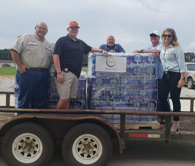 Local officials partnered with Iberville Safety and Construction Supply to provide pallets of water to the first responders in Lake Charles. Pictured are, from left: Sheriff Brett Stassi, Deputy Brandon Miller, Plaquemine Police Chief Kenny Payne, ISCS owner Terry Hebert and ISCS manager Mary Ellen Dupont.