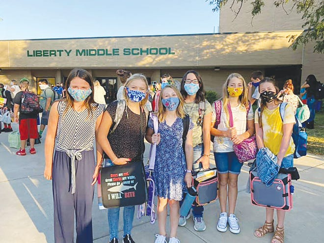 Liberty Middle School sixth and seventh grade students (from left) Madilyn Bolen, Sydney Riley, Taylor creadick, Morgan McGreevy, Savannah Copus, Lliana Craft pause for a first-day-of-school photo before going into their building on Wednesday, August 26, 2020.