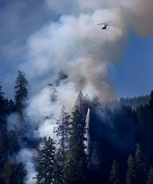 A helicopter drops water on The Sweet Creek Milepost 2 Fire near Mapleton Sept. 1, 2020.