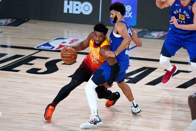 Utah's Donovan Mitchell (45) tries to drive around Denver's Jamal Murray during the second half of Sunday's playoff game in Lake Buena Vista, Fla. The two teams meet again Tuesday night in Game 7 of their first-round series. (AP Photo/Ashley Landis)