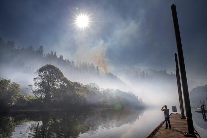 Smoke hangs over the Siuslaw River at Mapleton as the The Sweet Creek Milepost 2 Fire burns on the hillside overlooking the Oregon town Tuesday Sept. 1, 2020.