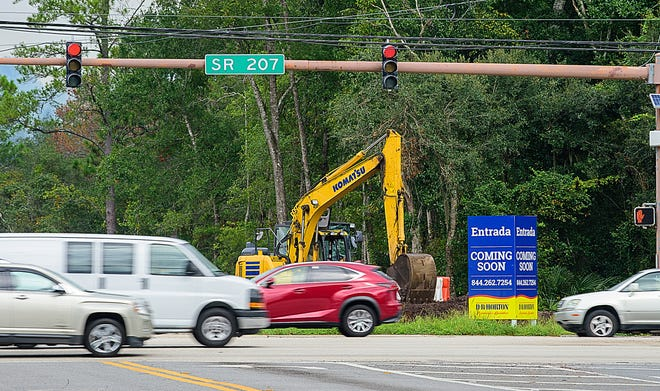 Vehicles on State Road 207 at Wildwood Drive pass the entrance of the Entrada development that is under construction in St. Augustine on Tuesday