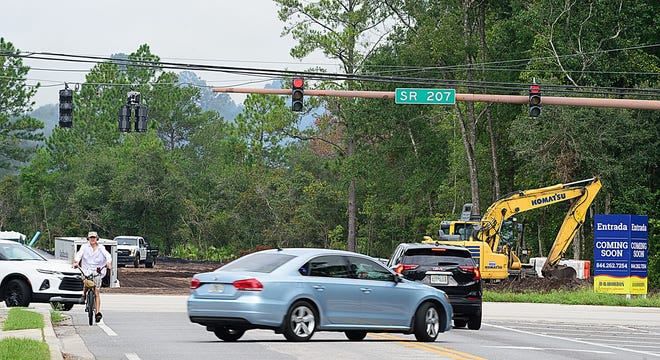Vehicles on State Road 207 at Wildwood Drive pass the entrance of the Entrada development that is under construction in St. Augustine on Tuesday. The community is approved for more than 900 homes. On Tuesday, the St. Johns County Commission approved the creation of the Entrada Community Development District, which will cover about 144 acres over portions of the Entrada PUD. The CDD boundaries may be expanded as the development is built out to include about 321 more acres. The CDD, which is a separate special district in the county, will pay for the development's amenities without making it the responsibility of general taxpayers in St. Johns County.