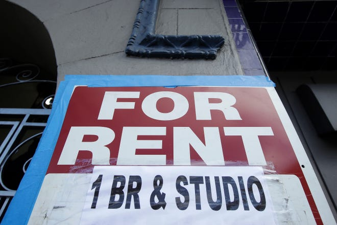 "A ""for rent"" sign is shown outside of a property."