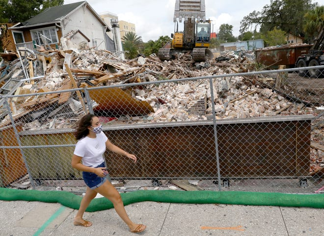 A woman walks past the rubble of what was a shopping plaza near The Swamp Restaurant on Aug. 24.