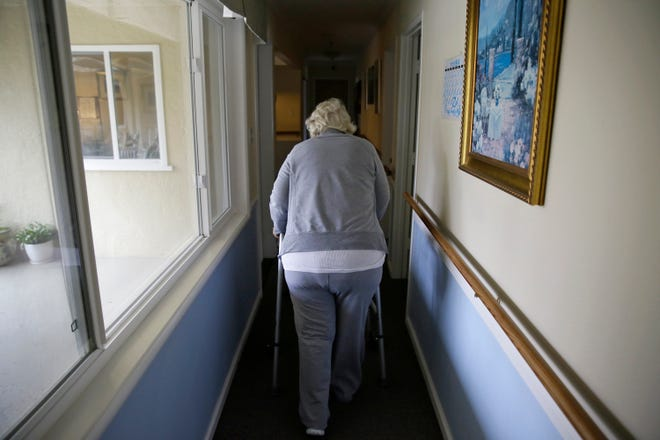 A woman walks to her room at a senior care home.