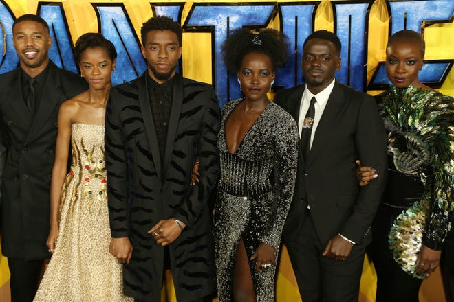 "FILE - In this Feb. 8, 2018 file photo, actors Michael B. Jordan, Leitia Wright, Chadwick Boseman, Lupita Nyong'o, Daniel Kaluuya and Danai Gurira pose for photographers upon arrival at the premiere of the film ""Black Panther"" in London. Boseman, who played Black icons Jackie Robinson and James Brown before finding fame as the regal Black Panther in the Marvel cinematic universe, has died of cancer. His representative says Boseman died Friday, Aug. 28, 2020 in Los Angeles after a four-year battle with colon cancer. He was 43.  (Photo by Joel C Ryan/Invision/AP, File)"