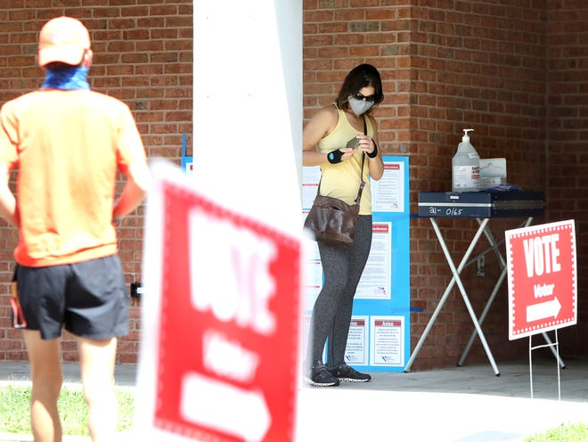 With masks and sanitizer at the ready, voters get in line to cast their ballots on Aug. 18 outside the Millhopper Library in Gainesville.