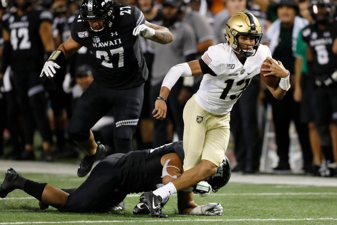 Army quarterback Christian Anderson (13) gets tripped up by Hawaii linebacker Darius Muasau (53) during the second half of an NCAA college football game Saturday, Nov. 30, 2019 in Honolulu. (AP Photo/Marco Garcia)