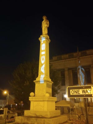 A message is projected onto the Confederate monument in Graham. The city has resisted calls to remove it.
