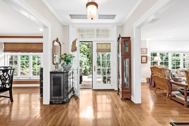 The foyer features an open layout with wood flooring and custom front doors.