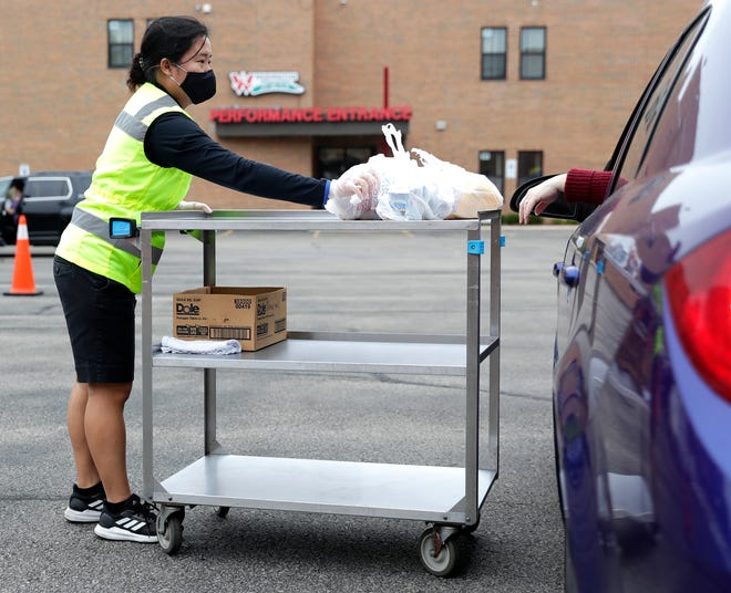 Ginger Soung, food service worker for the Green Bay Area Public School District, passes meals to a driver at Washington Middle School on Aug. 31. Because of COVID-19 concerns, meals had be more shelf-stable, easier to pack, deliver and transport.