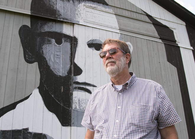 Art professor Doug Tyler poses Friday, Aug. 14, 2020 next to the mural he painted at the Hartland Township farm of Tom Keegan in 1976. The story of Tyler's barn murals, and a photo of Keegan posing similarly in front of the same mural, was featured on the front page of the Livingston County Daily Press & Argus in its first edition 20 years ago.