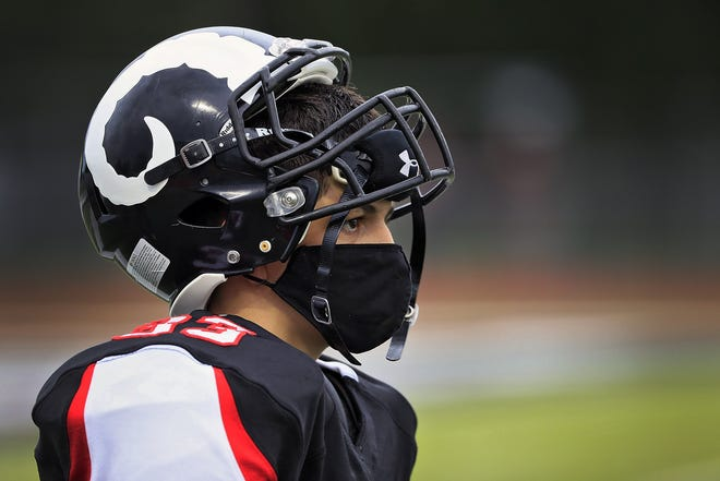In Ohio, players have to wear masks on the sidelines if their helmets aren't on. In Michigan, they'll have to wear them while playing on the field. Health experts say it's safe to breathe through a mask during a game.