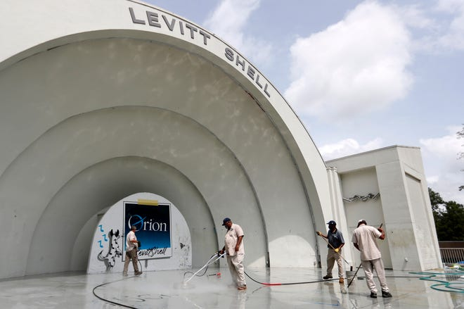 Mike Gateley, John Billings, Maurice Goode and Dennis Douglas clean BLM and other tags off the Levitt Shell after it was discovered Tuesday morning, Sept. 1, 2020, in Memphis, Tenn. Both the Levitt Shell in Overton Park and the walls surrounding Graceland were tagged overnight.
