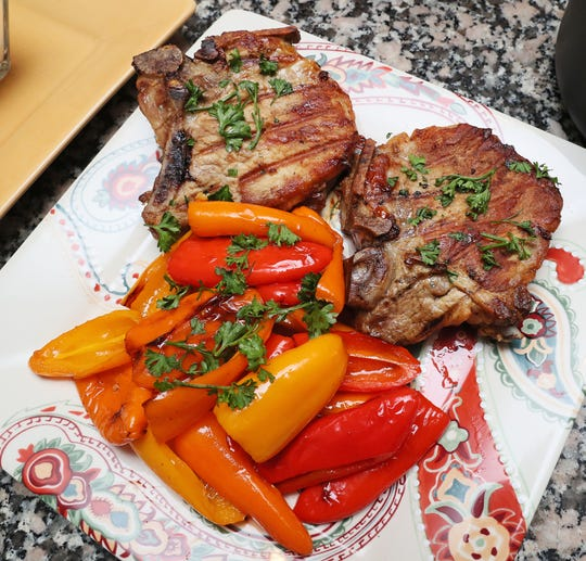 LeRoy's Rosemary Pork Chops are served with vegetables.