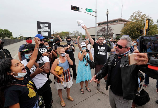 Virgil Roland, a  President Trump supporter from McHenry County, Illinois, makes a FaceTime live video as he argues with  Black Lives Matter members  chanting early Tuesday, Sept. 1, 2020, in Kenosha.