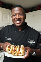 LeRoy Butler shows a plate of his LeRoy Leaps Green 'n Gold Game Day Brats