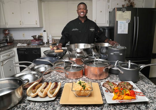 Former Packer LeRoy Butler poses in his kitchen with some of his favorite dishes and cookware. From left are his LeRoy Leaps Green 'n Gold Game Day Brats, 5-cheese Creamy Mac'n Cheese and  Rosemary Pork Chops.
