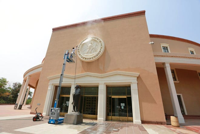 A maintenance worker power-washes the state seal at an entrance of the capitol building on Monday, Aug. 24, 2020, in Santa Fe, New Mexico. The building has been closed to the public since the onset of the coronavirus pandemic. Legislative meetings and gubernatorial addresses are broadcast online.