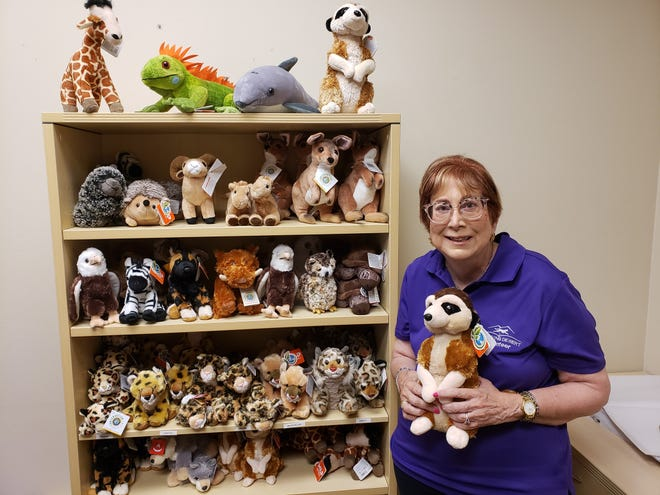 Marlene Binder holds a plushie of a meerkat, one of the animals available for symbolic adoption.