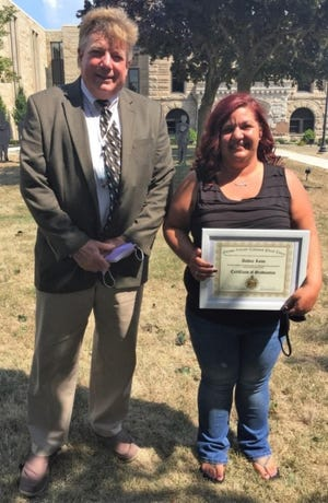 Ashley Lowe, one of four recent graduates of the Ottawa County Common Pleas Court's specialized docket programs, poses for a photo with Judge Bruce Winters, who credited her for working hard and having a good attitude.