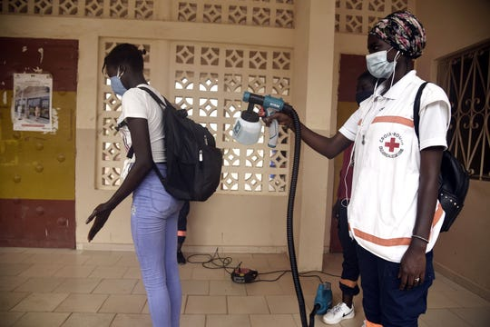 A Red Cross worker sprays a pupil with a disinfectant at the entrance of a school in Dakar on June 25, 2020, on the opening day of the classes for the students in the examination class in Senegal.