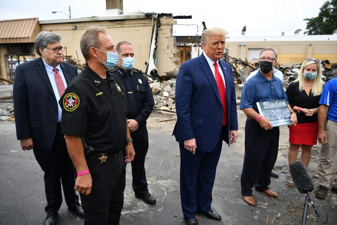 President Donald Trump and Attorney General William Barr tour an area affected by civil unrest in Kenosha, Wis., on Sept. 1.
