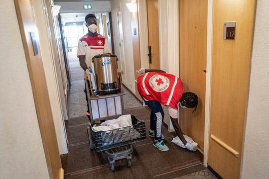 Senegalese Red Cross volunteers distribute food to people who are under a 14-day quarantine because they had been in contact with confirmed cases of the new coronavirus, at a hotel that has been taken over as a quarantine center, in Dakar, Senegal Sunday, April 19, 2020.