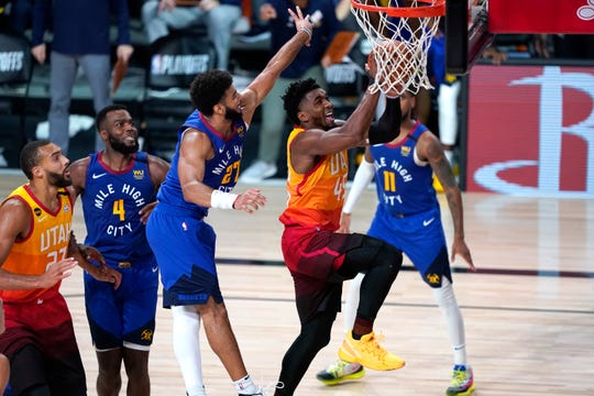 The Utah Jazz's Donovan Mitchell (45) goes up for a shot as the Denver Nuggets' Jamal Murray (27) defends during Game 4.