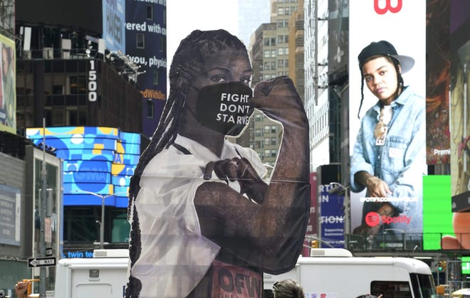 """A statue of """"Elena the Essential Worker"""" stands in New York's Times Square."""
