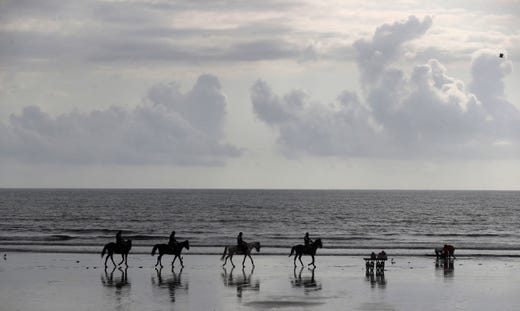 Policemen on horse backs patrol on the Arabian Sea coast as volunteers immerse idols of elephant headed Hindu god Ganesha marking the end of the 10-day long Ganesh Chaturthi festival in Mumbai, India, Tuesday, Sept. 1, 2020. Due to the COVID-19 pandemic authorities have restricted access for devotees for this annual event.