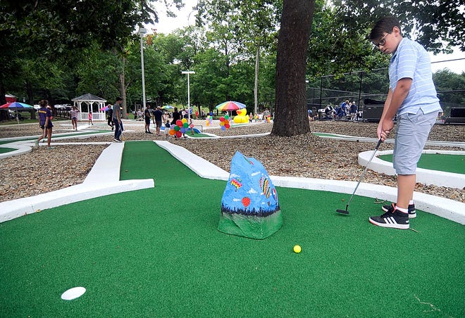 Ethan McArdle plays a hole at the Brookside Miniature Golf Course during its grand reopening after the renovations on Tuesday.
