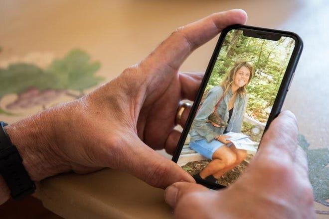 Paul Stringer shows a photo of his daughter, Kim Stringer, taken last September in the Adirondacks. [MICHELE HADDON / PHOTOJOURNALIST]