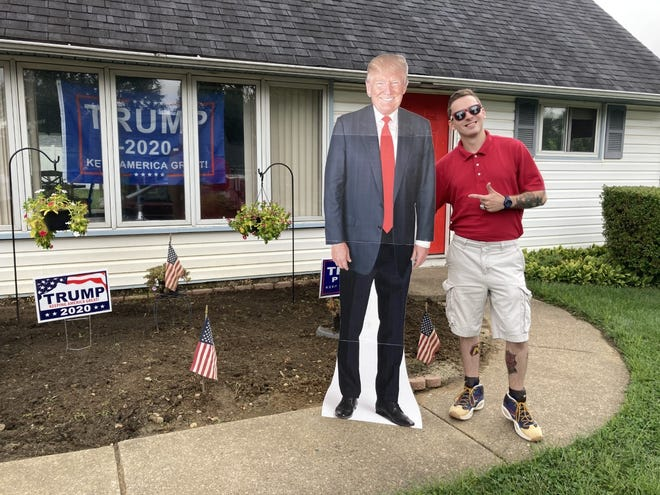 Ryan Erney, 26, of Levittown, Pa., poses with life-sized President Trump. Someone who disliked  Erney's support for the president left a bizarre message on his lawn.