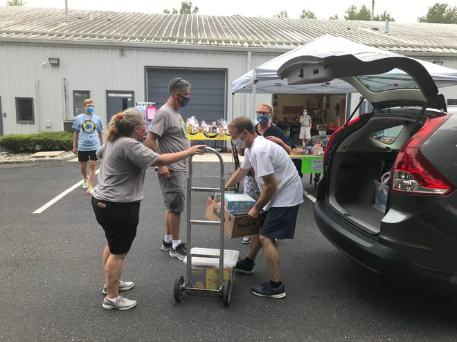 BookSmiles volunteers stack up boxes of books on a dolly during their book giveaway event Friday in Cherry Hill.
