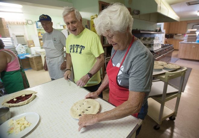 Fritz Retsch watched Nancy Klein flute the edge of a cherry pie Tuesday at the Big Knob Grange in New Sewickley Township.  About 10 volunteers made 40 cherry and 60 coconut cream pies to serve with a takeout stuffed pork chop dinner Thursday. Normally, fairgoers would have dined in the grange hall, but COVID-19 canceled this year's fair. [Sally Maxson/For BCT]